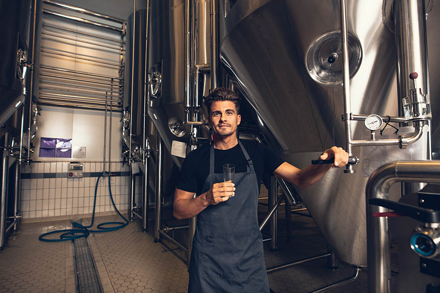 Business Insurance - Young Brewery Owner in Black Shirt and Gray Apron Holds a Beer Sample as He Poses in Front of Large Steel Brewing Tanks
