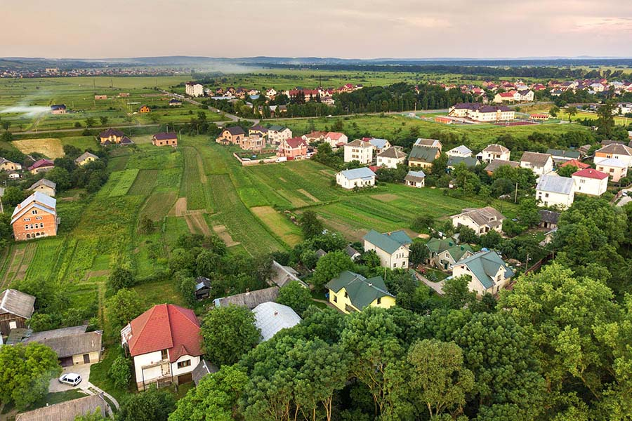 Butler, PA Insurance - Aerial View of Suburban Homes, Trees and Farmland With Blue Mountains in the Distance on a Hazy Summer Day