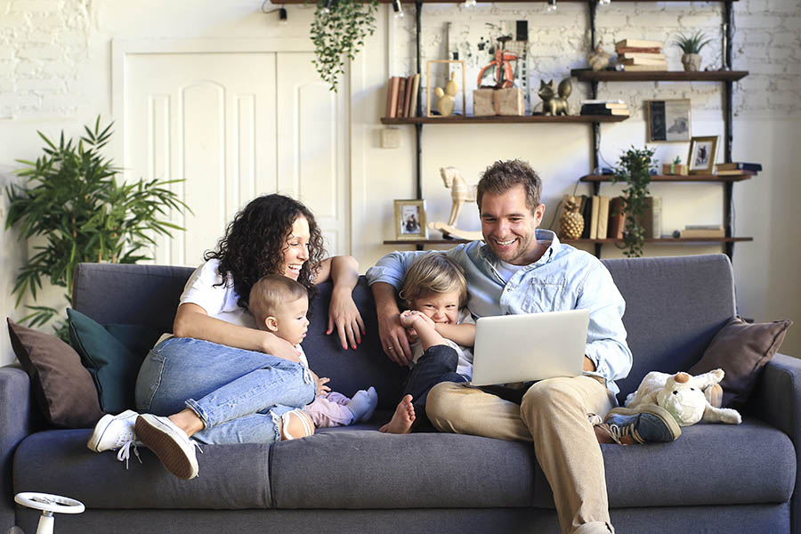 Personal Insurance - Mother, Father, Toddler, and Baby Laugh and Use a Laptop on a Blue Couch in Their Cozy Living Room Filled With Books and Plants