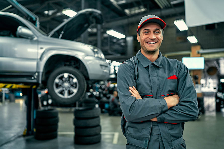 Specialized Business Insurance - Auto Mechanic Smiles and Crosses His Arms With an Elevated Car and Spare Tires Stacked Behind Him in His Large High End Auto Shop